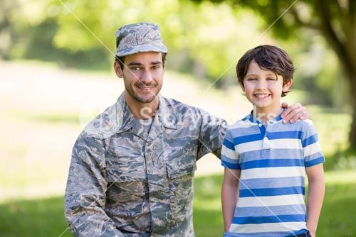 Army soldier with boy in park