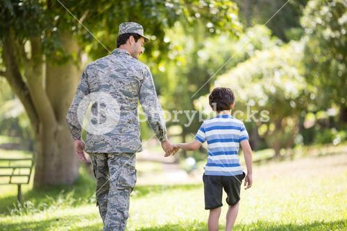 Army soldier walking with boy in park