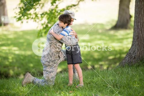 Army soldier embracing boy in park