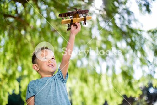 Boy playing with a toy aeroplane in park