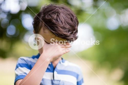 Boy covering eyes with hand in park