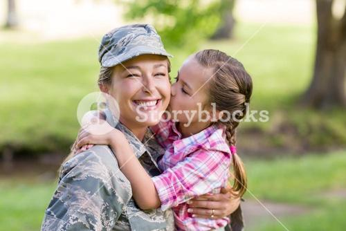 Happy female soldier being kissed by her daughter in park