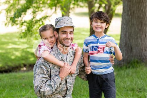 Happy soldier with his son and daughter in park