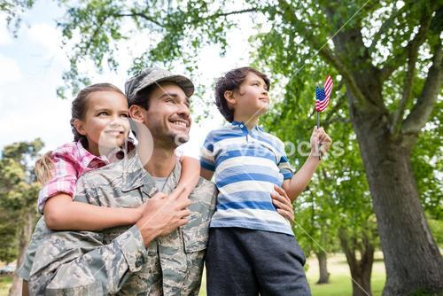 Happy soldier reunited with his son and daughter in park
