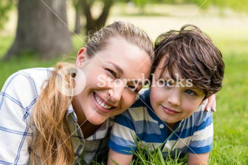 Happy mother and son lying in park