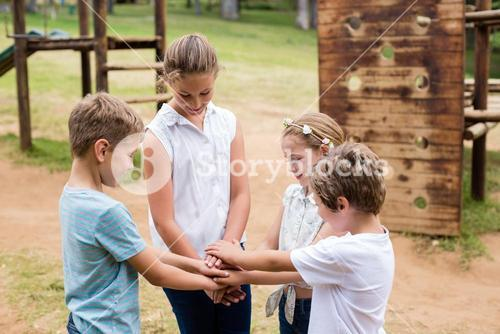 Kids forming hand stack in park