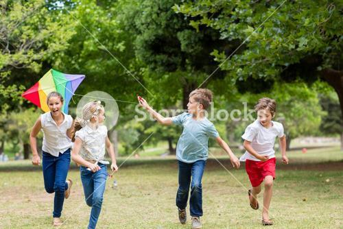 Kids playing with a kite in park