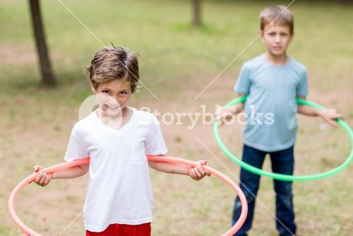 Two boys playing with hula hoop