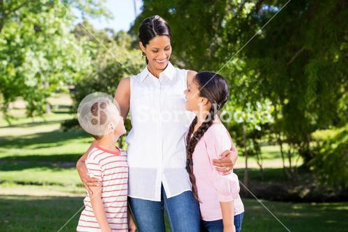 Mother and kids interacting with each other in park