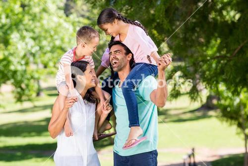 Parents carrying their children on shoulder in park