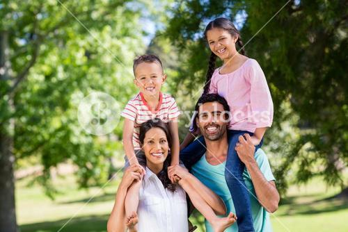 Portrait of parents carrying their children on shoulder in park