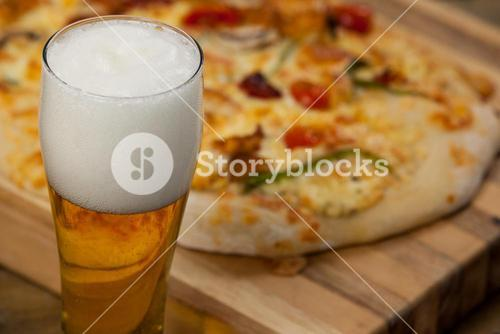 Delicious pizza served on pizza tray with a glass of beer