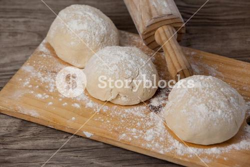 Rolling pin with pizza dough and flour on chopping board