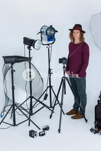Photographer with hands in pocket standing in the photo studio