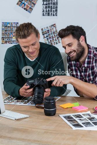 Photographers reviewing captured photos in digital camera