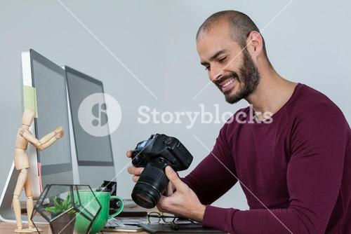 Photographer reviewing captured photos in his dslr camera