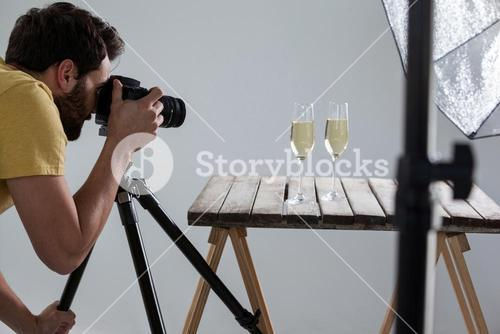 Male photographer photographing champagne glasses