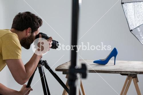 Male photographer photographing footwear