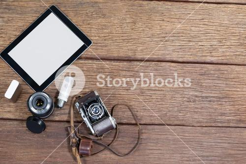 Close-up of old fashioned camera, lens, bulb, digital tablet on table