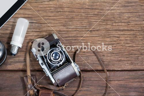 Close-up of old fashioned camera, lens, bulb on table