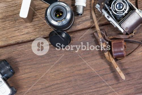 Close-up of old fashioned cameras, lens, bulb on table