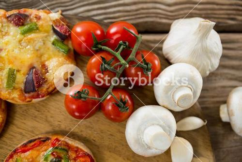 Pizza, tomato, and garlic on a wooden tray