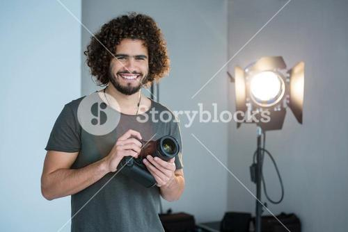 Happy photographer holding a camera in the studio