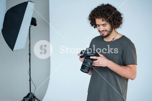 Photographer looking at captured photos in his digital camera