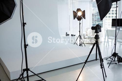 Photo studio with tripod, lighting equipment and digital camera