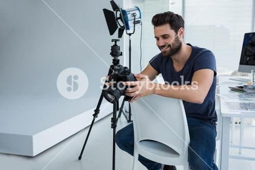 Photographer reviewing captured photos in his digital camera