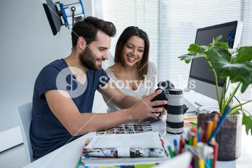 Photographers reviewing captured photos in his digital camera
