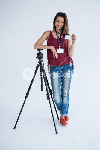 Portrait of female photographer showing identity card