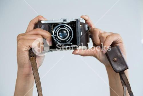 Close-up of female photographer holding old fashioned camera