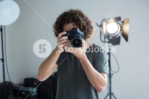Male photographer with digital camera in studio