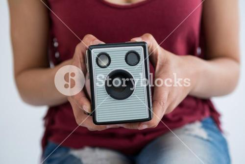 Mid section of female photographer holding old fashioned camera
