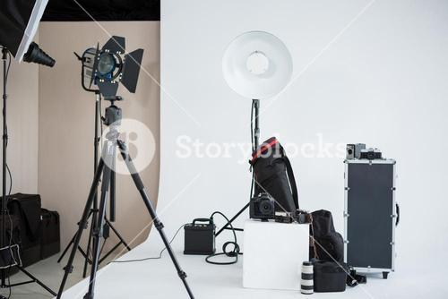Photo studio with lighting equipment and digital camera
