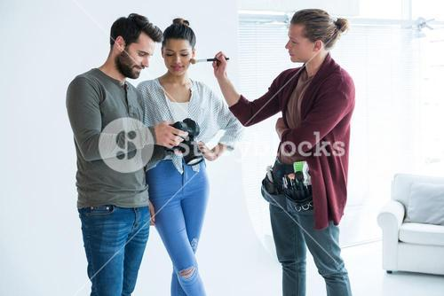 Photographers and female model looking at images on the camera display