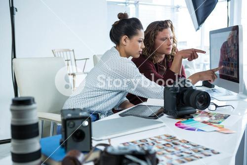 Photographers working over computer