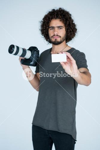 Male photographer showing visiting card in studio