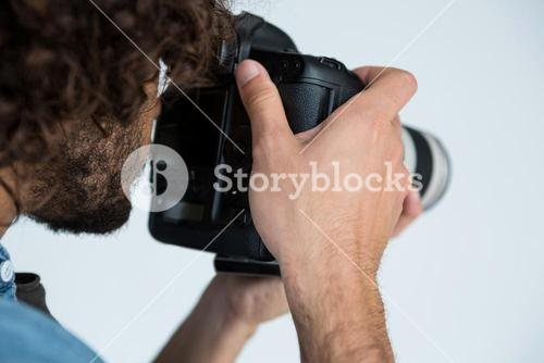Photographer with digital camera in studio