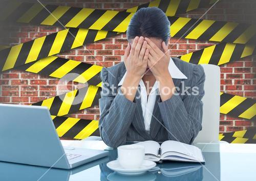 Tensed businesswoman sitting with hand on forehead against brick wall