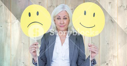 Senior businesswoman holding smiley faces against wooden background