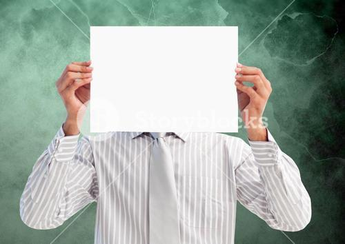 Businessman holding blank placard in front of his face against green background