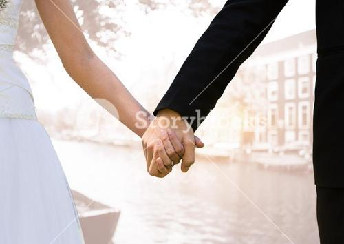 Newly wed couple holding hands against city in background