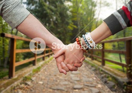 Couple holding hands against park in background