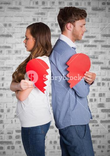 Depressed couple holding broken heart against brick wall