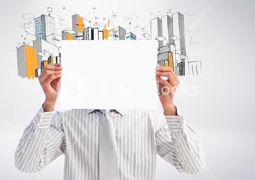 Businessman holding blank placard in front of his face against hand drawn office buildings in backgr