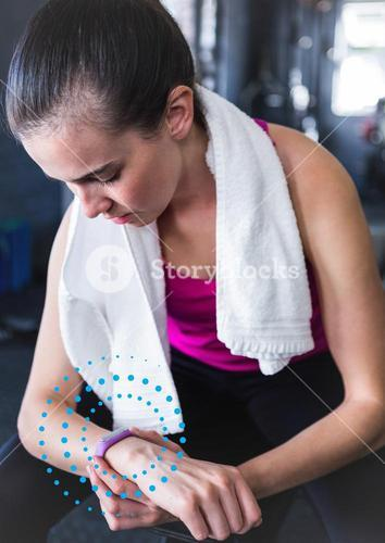 Fit woman using fitness band in gym against spiral dots in background