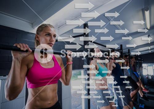 Fit woman performing pull up exercise in gym against direction arrows in background