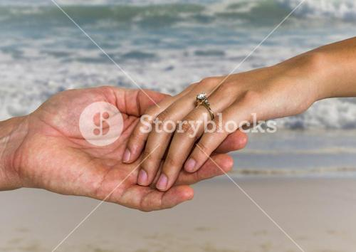 Newly wed couple holding hands on beach